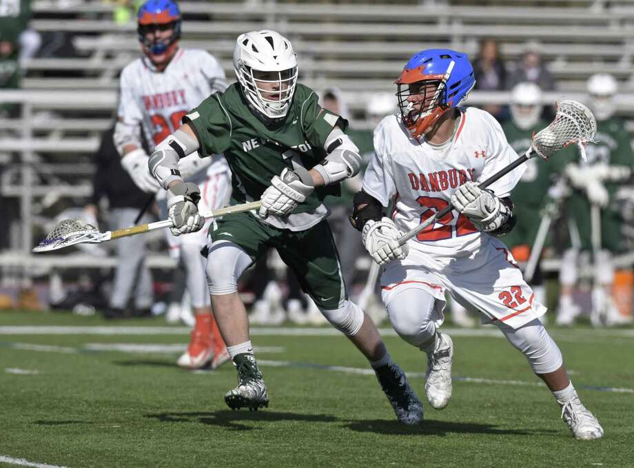 Danbury's Marson Rivers (22) is shadowed by New Milford's Jacob Anderson (1) as he moves with the ball in their game on Friday at Danbury High School. The Hatters won 7-4. Photo: H John Voorhees III / Hearst Connecticut Media / The News-Times