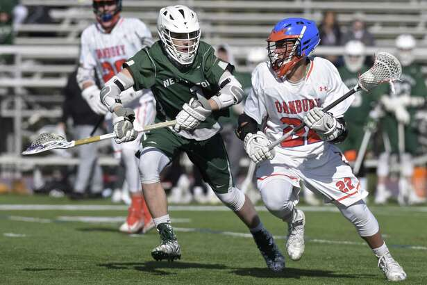 Danbury's Marson Rivers (22) is shadowed by New Milford's Jacob Anderson (1) as he moves with the ball in their game on Friday at Danbury High School. The Hatters won 7-4.