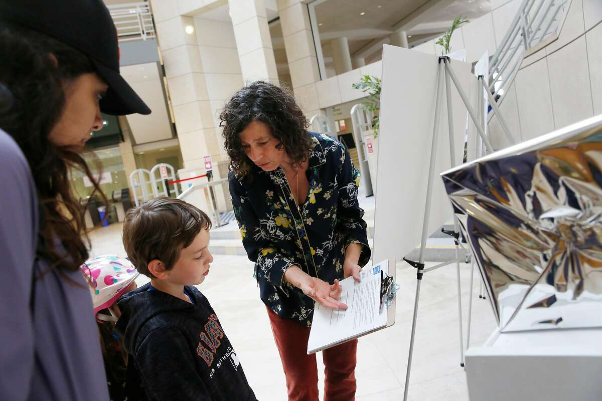 Beth Rubenstein (right) , special projects manager, building design and contruction, San Francisco Public Works explains a form for public feedback to Anahi Palomares (left) and Judah Franco, 8 (center) as a display of designs for replacement of San Francisco's on-street public toilets by three finalists at the main library in San Francisco, Calif., on Tuesday, April 24, 2018.
