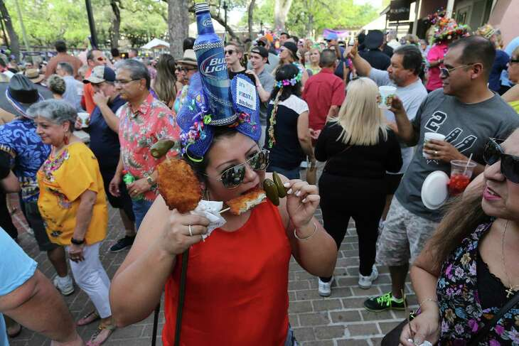 Raquel Rother takes a bite of her chicken-on-a-stick at NIOSA in 2018. All of Fiesta has been canceled this year out of concern for the spread of the coronavirus through crowds.
