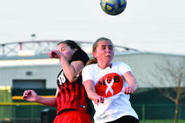 Edwardsville's Zoe Ahlers, right, goes up for a head ball during the first half of Tuesday's SWC game against Granite City.
