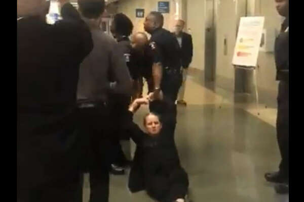 Woman is dragged out of HISD meeting by police.