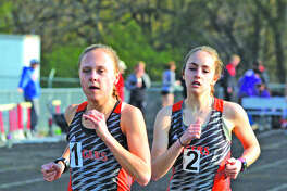 Edwardsville's Abby Schrobilgen, left, and Hannah Stuart placed first and second, respectively, in the 3,200-meter run in Tuesday's Madison County Large School Meet at Highland.