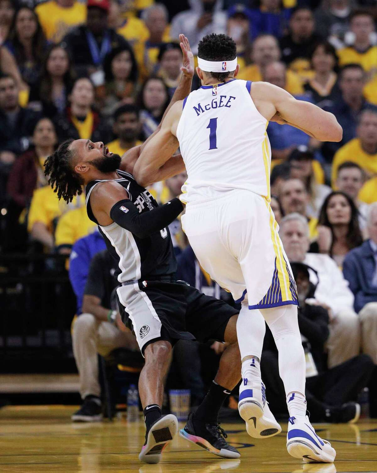 San Antonio Spurs' Patty Mills tries to defend against Golden State Warriors' JaVale McGee in the first quarter during game 5 of round 1 of the Western Conference Finals at Oracle Arena on Wednesday, April 25, 2018 in Oakland, Calif.