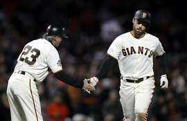 San Francisco Giants' Mac Williamson, right, shakes hands with third base coach Ron Wotus after Williamson's solo home run against the Washington Nationals during the sixth inning of a baseball game Tuesday, April 24, 2018, in San Francisco. (AP Photo/Marcio Jose Sanchez)