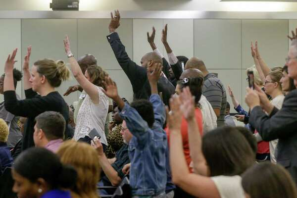 People wave their hands in response to a speaker during the Houston ISD board meeting Tuesday, April 24, 2018. The trustees were scheduled to vote on whether to hand over control of 10 chronically low-performing schools to Energized For STEM Academy, which already runs four in-district HISD charters. Many of the large crowd attending the meeting are against the partnership.