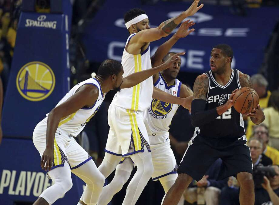 San Antonio Spurs' LaMarcus Aldridge, right, looks to pass the ball away from Golden State Warriors' Kevin Durant, left, JaVale McGee, and Andre Iguodala (9) during the first half in Game 5 of a first-round NBA basketball playoff series Tuesday, April 24, 2018, in Oakland, Calif. (AP Photo/Ben Margot) Photo: Ben Margot, STF / Associated Press / Copyright 2018 The Associated Press. All rights reserved.