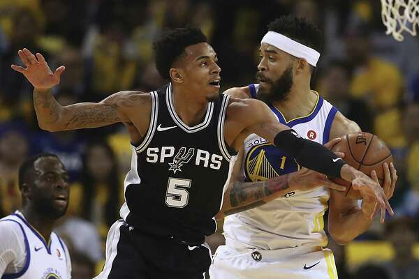 Golden State Warriors' JaVale McGee, right, keeps the ball from San Antonio Spurs' Dejounte Murray (5) during the first half in Game 5 of a first-round NBA basketball playoff series Tuesday, April 24, 2018, in Oakland, Calif. (AP Photo/Ben Margot)
