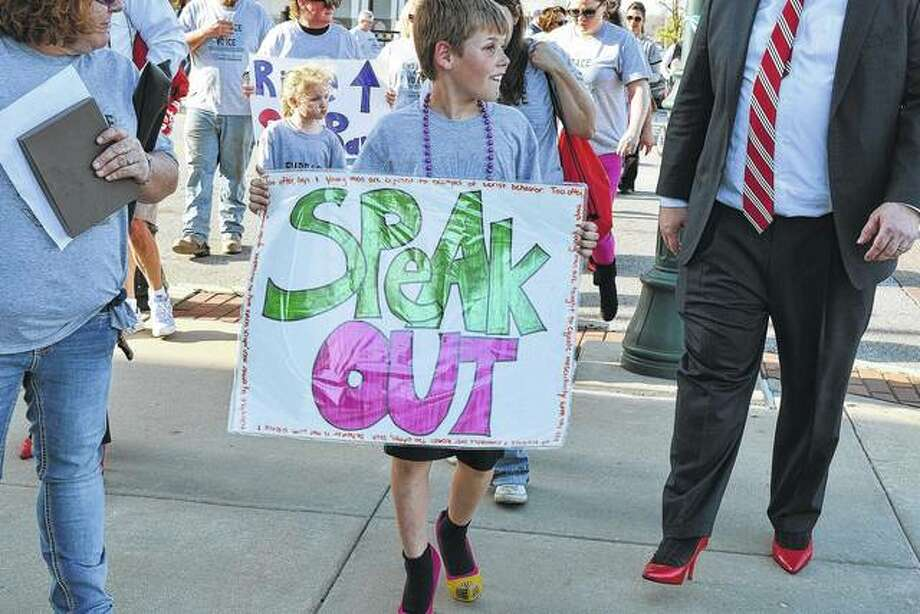 Seth Dober, 9, the son of Jessica Cowgur and Cassidy Dober of Jacksonville, walks Tuesday in the 11th annual Walk A Mile in Her Shoes event in downtown Jacksonville. The event helps raise awareness of sexual assault and benefits the Prairie Center Against Sexual Assault.