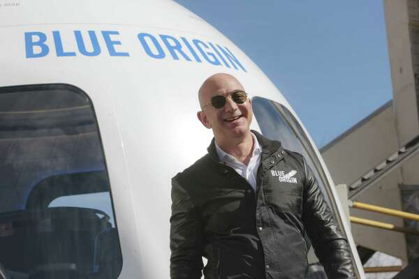 Jeff Bezos, chief executive officer of Amazon.com and founder of Blue Origin, smiles while speaking at the unveiling of the Blue Origin New Shepard system during the Space Symposium in Colorado Springs, Colorado, on April 5, 2017.