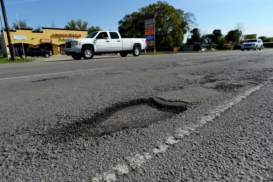 Cars drive past a pothole on Nederland Avenue, Monday, March 19, 2018. Photo taken Monday 3/19/18 Ryan Pelham/The Enterprise Photo: Ryan Pelham / ©2017 The Beaumont Enterprise/Ryan Pelham