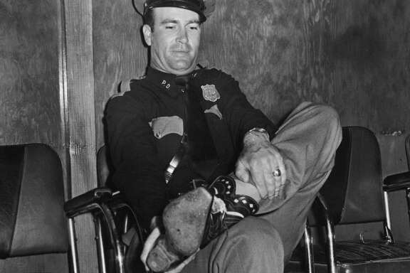 """04/1948 - Patrolman Reno Kirby gloomily prepares to say goodbye to his cherished cowboy boots, after he was """"ordered"""" by the Madisonville Sidewalk Cattlemen's Association either to doff the boots """"forthwith"""" or establish his eligibility to sport boots by proving ownership of at least two cows. """"I ain't got a cow to my name,"""" Kirby confessed. """"It looks like barefoot for me."""""""