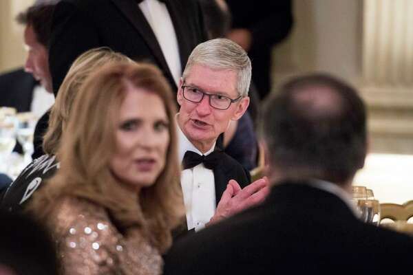 Apple CEO Tim Cook chats with guests Tuesday night at the White House state dinner for French President Emmanuel Macron and his wife, Brigitte Macron.
