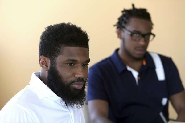Rashon Nelson, listens to a reporter's question alongside Donte Robinson during an interview with the Associated Press Wednesday April 18, 2018 in Philadelphia. Their arrests at a local Starbucks quickly became a viral video and galvanized people around the country who saw the incident as modern-day racism. In the week since, Nelson and Robinson have met with Starbucks CEO Kevin Johnson and are pushing for lasting changes to ensure that what happened to them doesn't happen to future patrons. They are also still processing what it means to have had an everyday encounter escalate into a police confrontation. (AP Photo/Jacqueline Larma)