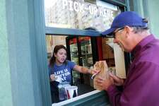 Katharine Woodward hands  Rich Breksa, of Stamford, his order on Walter's Hot Dogs first day open at Commons Park in the Harbor Point area of Stamford, Conn. on Thursday, Oct. 12, 2017.