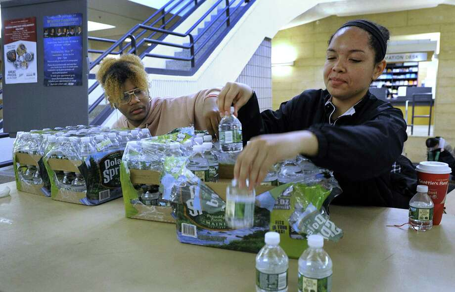 Javon Weaver, 19, left, and Anna Adebambo, 18, of Danbury, work a desk set up by the Student Government with water bottles to give away to students and staff passing through the Student Center on the White Street campus of Western Connecticut State University Tuesday, April 25, 2018. They were also giving out emergency kits until they ran out - filled with snacks, disinfectant wipes and medical gloves. Photo: Carol Kaliff / Hearst Connecticut Media / The News-Times