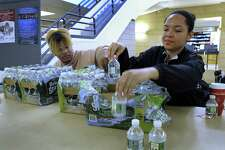 Javon Weaver, 19, left, and Anna Adebambo, 18, of Danbury, work a desk set up by the Student Government with water bottles to give away to students and staff passing through the Student Center on the White Street campus of Western Connecticut State University Tuesday, April 25, 2018. They were also giving out emergency kits until they ran out - filled with snacks, disinfectant wipes and medical gloves.