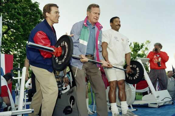 US President George Bush is assisted by movie star Arnold Schwarzenegger (L) and weightlifter Fairfax Hackley, as he lifts a barbell on May 1, 1991 on the south lawn of the White House during the second annual Great American Workout.