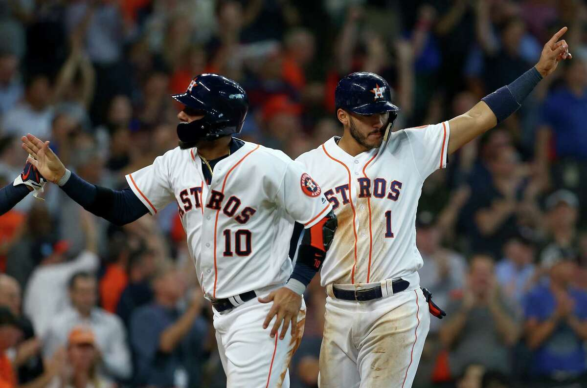 Houston Astros first baseman Yuli Gurriel (10) and shortstop Carlos Correa (1) celebrate after scoring off Alex Bregman's three-RBI triple during the fourth inning of an MLB game against the Los Angeles Angels at Minute Maid Park Wednesday, April 25, 2018, in Houston.