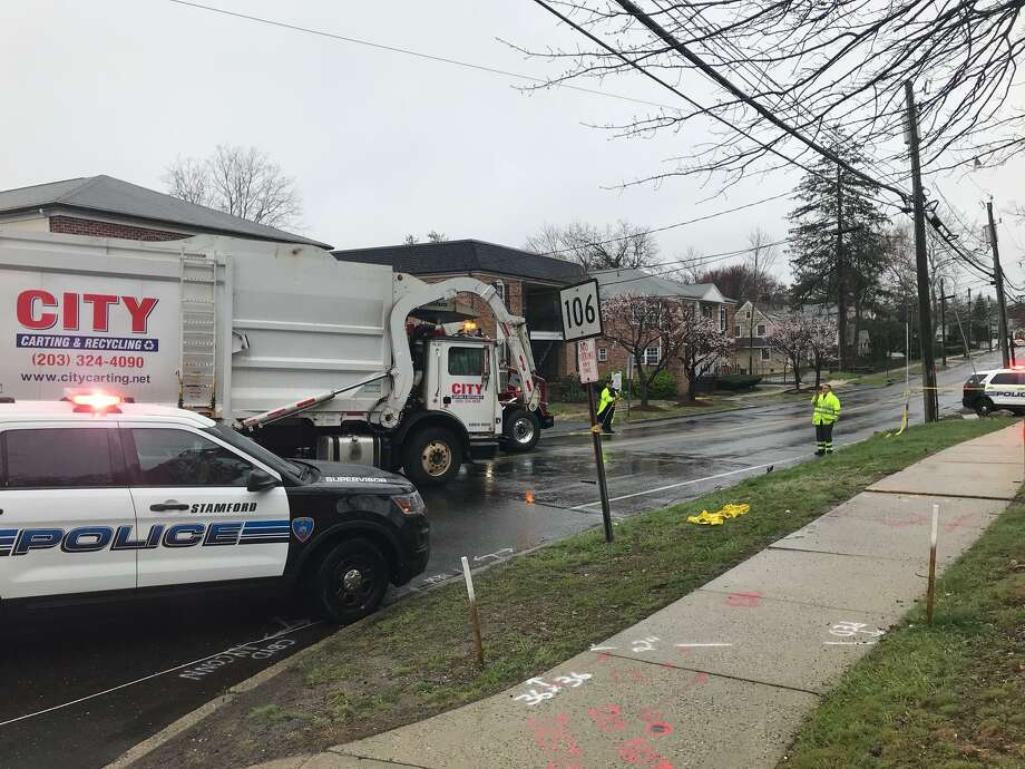 Police at the scene of a crash where a garbage truck struck and seriously injured a 25-year-old Stamford woman on Wednesday morning. Photo: John Nickerson / Staff