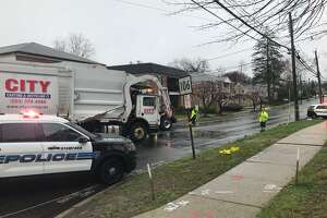 Police at the scene of a crash where a garbage truck struck and seriously injured a 25-year-old Stamford woman on Wednesday morning.