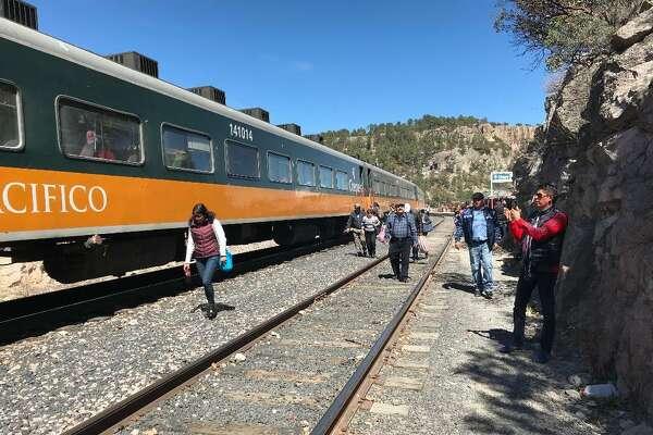 "Passengers walk alongside the ""El Chepe"" train at the stop at Divisadero, Mexico, next to Copper Canyon."