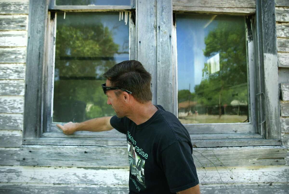 Kirt Haeberlein, owner of Pickers Paradise, inspects the condition of old wavy glass windows in the birth home of Country Western star Dale Evans.