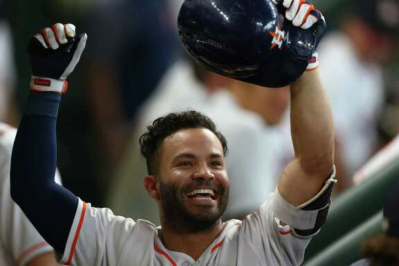 Houston Astros second baseman Jose Altuve (27) celebrates in the dugout after hitting a solo home run during the sixth inning of an MLB game against the Los Angeles Angels at Minute Maid Park Wednesday, April 25, 2018, in Houston.