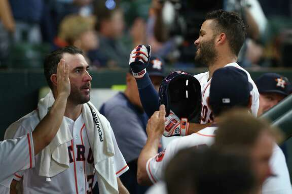 Houston Astros second baseman Jose Altuve (27) celebrates with teammates in the dugout after hitting a solo home run during the sixth inning of an MLB game against the Los Angeles Angels at Minute Maid Park Wednesday, April 25, 2018, in Houston.
