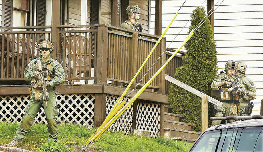 Members of the ILEAS Tactical Team stand on the front porch and surround a house they raided early Wednesday morning in the 1100 block of West Ninth Street in Alton. Dozens of tactical officers from the multi-jurisdictional agency, along with Alton police and Illinois State Police, raided the house and arrested one person without incident. A second person was arrested in a Chevrolet Tahoe on Piasa Street just south of East Fifth Street after they left the same house just as police arrived. Photo:       John Badman | The Telegraph
