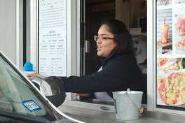 Adriana Martinez assists a customer with an order at AJ's Snowcones in Pearland Friday, Apr. 5.
