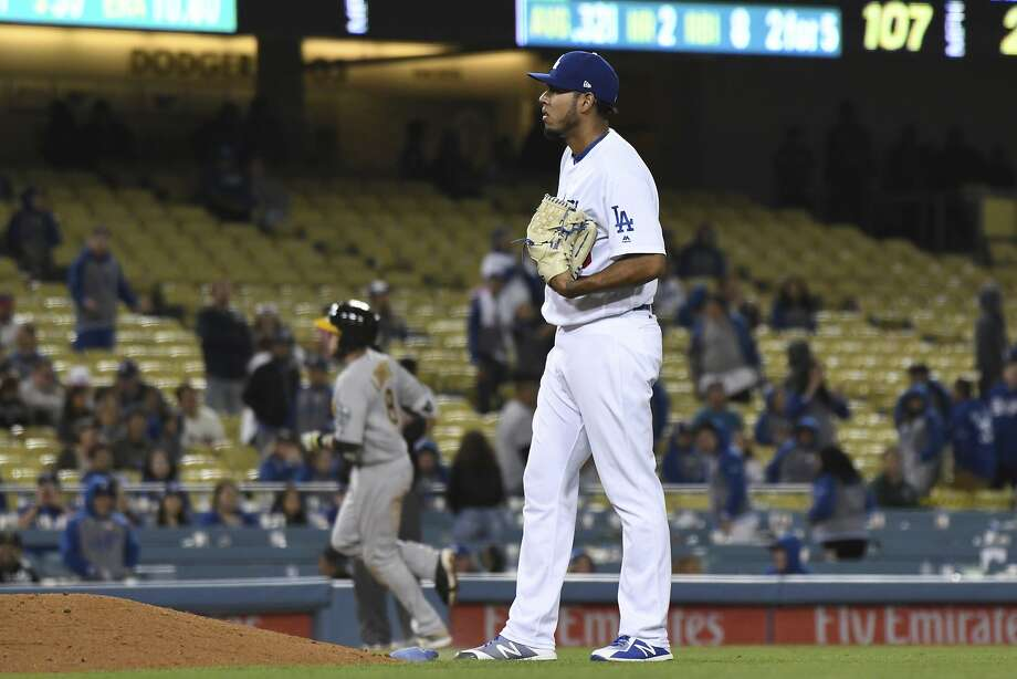 Los Angeles Dodgers relief pitcher Wilmer Font stands behind the mound as Oakland Athletics' Jed Lowrie rounds the bases after hitting a three-run home run during a baseball game Wednesday, April 11, 2018, in Los Angeles. (AP Photo/Michael Owen Baker) Photo: Michael Owen Baker / Associated Press