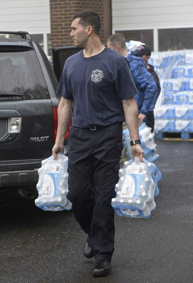 Danbury fire fighter Chris Moore carries cases of bottled water to a waiting car as the City of Danbury distributes donated bottled water at the Fire Department head quarters on New Street Wednesday afternoon. Residents have been asked not to drink city water without boiling it because of a water main break on Monday. April 25, 2018, in Danbury, Conn. Photo: H John Voorhees III / Hearst Connecticut Media / The News-Times