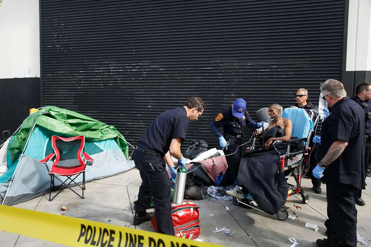 Emergency responders tend to a homeless man who was stabbed on Division Street after he moved from 13th Street on Wednesday, April 25, 2018 in San Francisco, Calif.