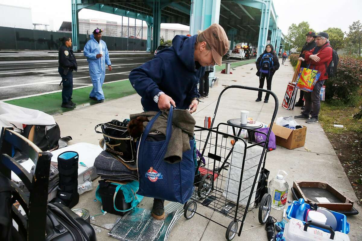 Krystle Erickson packs up her belongings along 13th Street as the street is cleared of tents in San Francisco, Calif., on Wednesday, April 25, 2018.