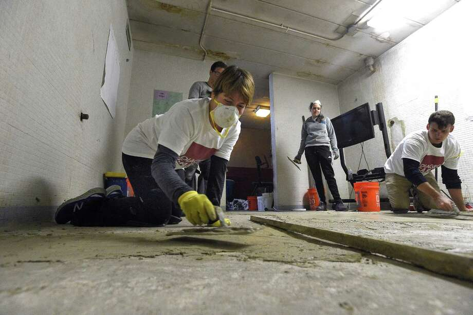 Tracy Rabuse of Norwalk, who works in sales and analytics spreads mortar on the floor of a locker room. Rabuse, along with 100 Diageo North America volunteers participated in a community service day and revitalization project at Domus Kids in Stamford, Conn. on April. 25, 2017.  The group of employees from the finance and human resources departments perform interior and exterior beautifications and structural improvements projects. Photo: Matthew Brown / Hearst Connecticut Media / Stamford Advocate