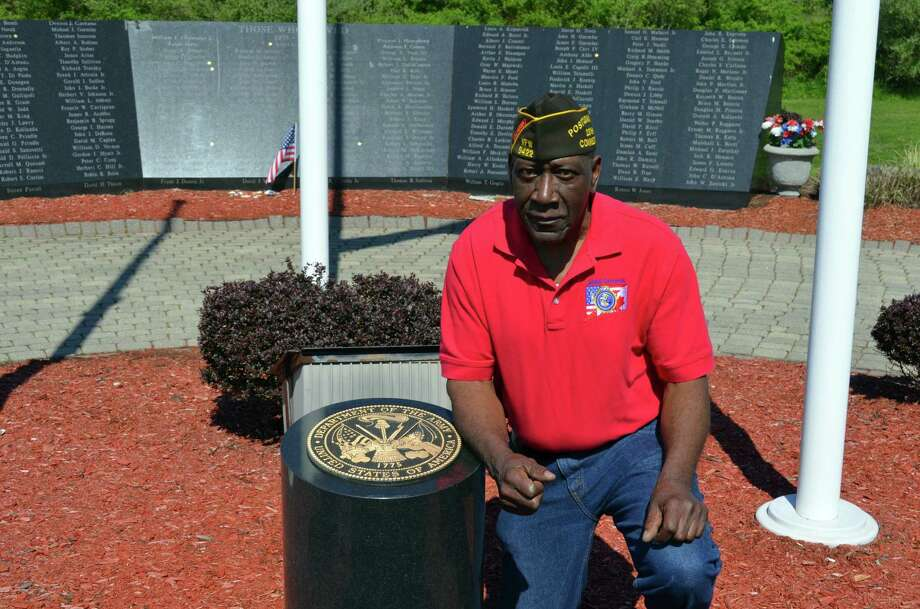 Freddy Jackson, commander of Veterans of Foreign Wars Post 9422, kneels beside the granite U.S. Army insignia marker May 11, 2016, at the Vietnam Veterans Memorial in Bradley Point Park. Jackson, an Army vet who served in Colorado and Korea in 1963-66, will lead the 2018 Memorial Day parade as grand marshal when it steps off at 10:30 a.m. May 28, 2018 along Campbell Avenue. Jackson was selected to steer the 2016 and 2017 parades, but they were canceled by rain. There is no rain date for this year's parade. Photo: Contributed / Michael P. Walsh / City Of West Haven