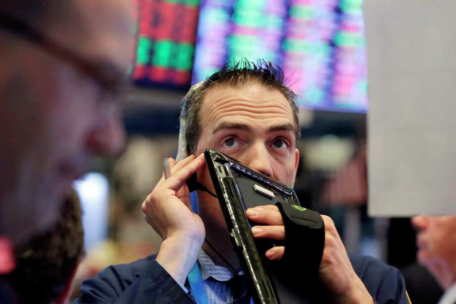 Trader Gregory Rowe works on the floor of the New York Stock Exchange, Wednesday, April 25, 2018. Stocks are opening lower, extending the market's losses, after several companies reported weak results or warned of higher costs. (AP Photo/Richard Drew) Photo: Richard Drew / AP
