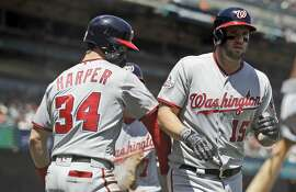 Washington Nationals' Matt Adams, right, is met at home plate by teammate Bryce Harper after Adams' three-run home run against the San Francisco Giants during the fourth inning of a baseball game Wednesday, April 25, 2018, in San Francisco. (AP Photo/Marcio Jose Sanchez)
