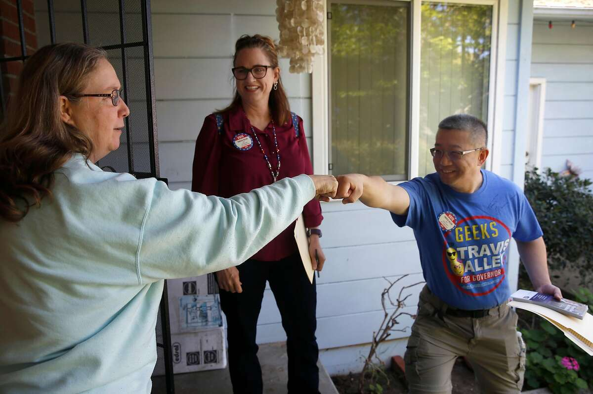 A registered voter (left) fist-bumps with Xiaoshan Song while he canvasses a neighborhood with Michele Guerra (center) for Republican gubernatorial candidate Travis Allen in Concord, Calif. on Saturday, April 21, 2018.