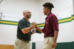 Athletic Director Randy Hollas, left, shakes hands with Zach Baker, who is signing with Earlham College for football, during the ceremony on Wednesday, April 25, 2018, at The Woodlands Christian Academy. (Michael Minasi / Houston Chronicle)