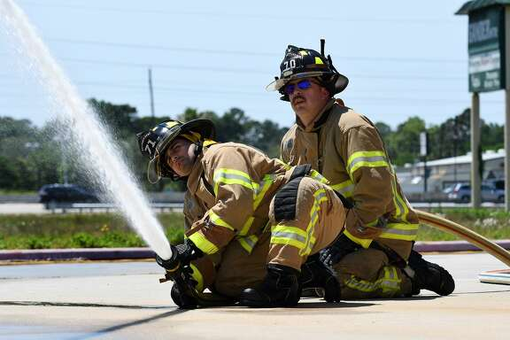 Spring Fire Dept. firefighters Gary Bowker, left, and Jeremey Cobb, from Station 71, work a hose during fire engine new driver training in the parking lot at Gander Mountain on I-45 near Cypresswood on April 24, 2018. (Photo by Jerry Baker/Freelance)