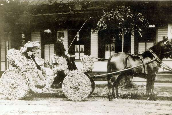 Col. and Mrs. Frank H. Bushick , Sr., in flower decorated carriage with driver for parade of Battle of Flowers, San Antonio , Texas , 1906. Frank Bushick was president of the Battle of Flowers ( or Fiesta ) Association at the time, and managing editor of the San Antonio Express. This picture given to Jean Dugat by her uncle, Gentry Dugat, on April 8, 1955.