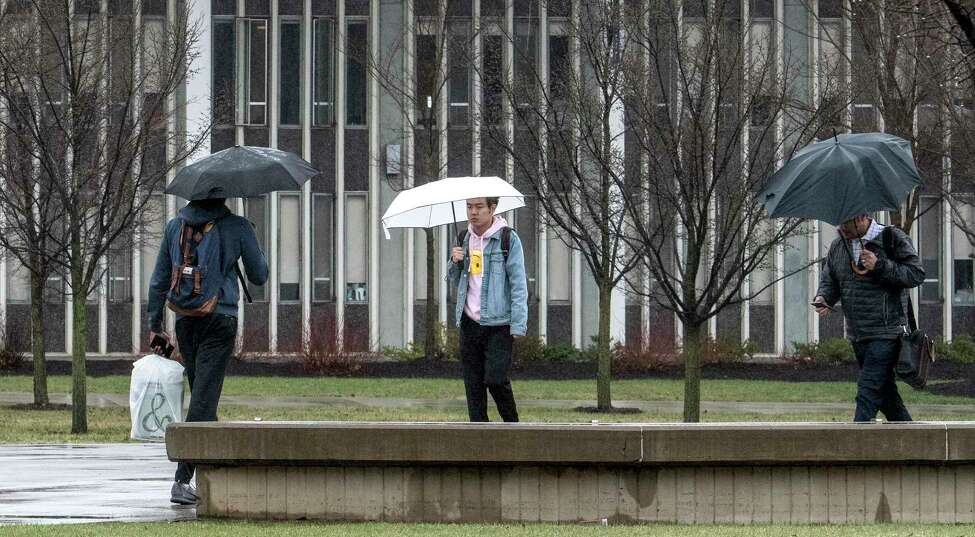 Students dodge the rain drops on the University at Albany campus on the way to class Wednesday April 25, 2018 in Albany, N.Y. (Skip Dickstein/Times Union)