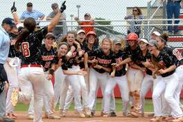 The Katy softball team waits at the plate for Corey Burrough (8) after her game-winning, two-run home run in game two of the Region III-6A semifinals May 21 at Katy High School. Visit HCNPics.com for more photos.