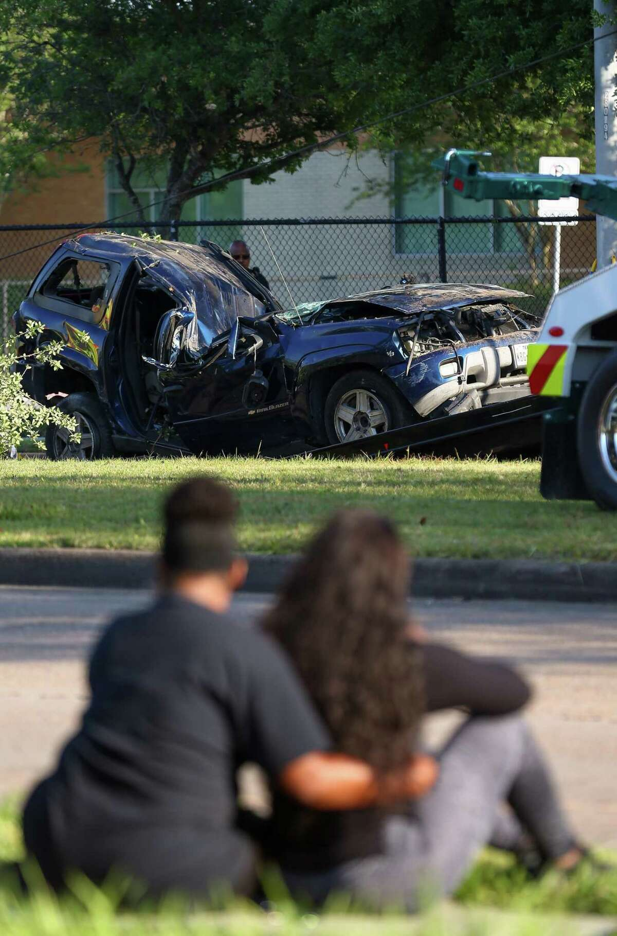 Shawna Jackson, foreground right, watches as a tow truck removes the vehicle her 15-year-old son Seviyon Farley died in during a two-vehicle crash on West Fuqua Street, near Bathurst Drive Wednesday, April 25, 2018, in Houston. Two teenage boys were killed in the wreck. ( Godofredo A. Vasquez / Houston Chronicle )