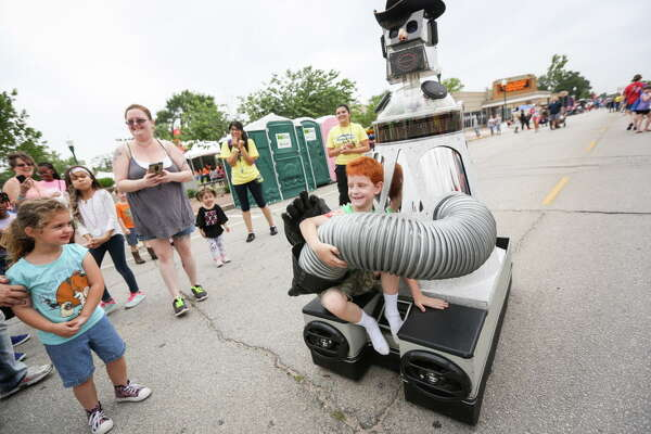 Blake White, 7, goes for a ride on a driving, talking, hand waving robot during KidzFest on Saturday, April 29, 2017, in downtown Conroe.