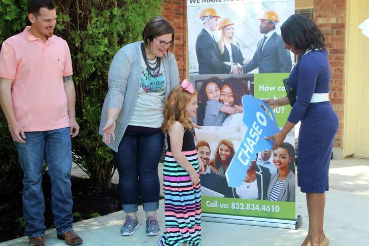 Kenya Burrell-VanWormer (right,) Chase affordable lending and relationship manager, hands a large ceremonial key to four-year-old Maggie Avant before she and her father, Drew Avant (left) and mother Jaclyn Avant (center) get to see the inside of their new finished home in Atascocita on Wednesday, April 25.