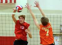 Fairfield Warde's Eli Feay (13) spikes the ball past Ridgefield's Thomas Groves (7) during boys volleyball action in Fairfield, Conn., on Wednesday Apr. 25, 2018.