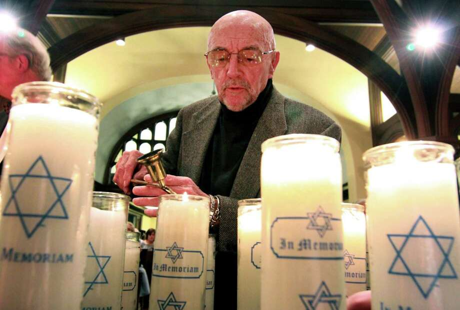 "Harry Weichsel lights a candle during Fairfield's 35th annual Holocaust Commemoration at First Church Congregational in Fairfield on Wednesday. At right, Holocaust survivor Endre ""Andy"" Sarkany speaks at the remembrance. Sarkany, who was born in 1936, lived in Budapest during WWII. Photo: Christian Abraham / Hearst Connecticut Media / Connecticut Post"
